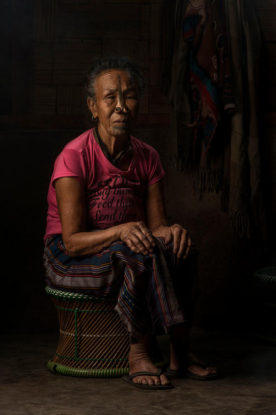"""Tilling Manu, 61. She lives in Hong Village, Ziro, India.  Manu was 3 yrs old when her ears were pierced, 7yrs old when she received her nose plug and tattooed at the age of 12 or 13. She didn't want to get the tattoos because she heard it was painful. She ran and hid under the house with the pigs until her parents pulled her out and tied her hands and legs before performing the act. When asked now about her tattoos and nose plug Manu says, """" I am very proud to have them because it is our own culture. I want to have these because everybody knows that I am Apatani""""."""