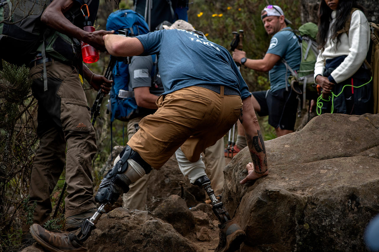 Scott West navigates the rough terrain with the help of his guides on August 5, 2021 during his trek to summit Mount Kilimanjaro.