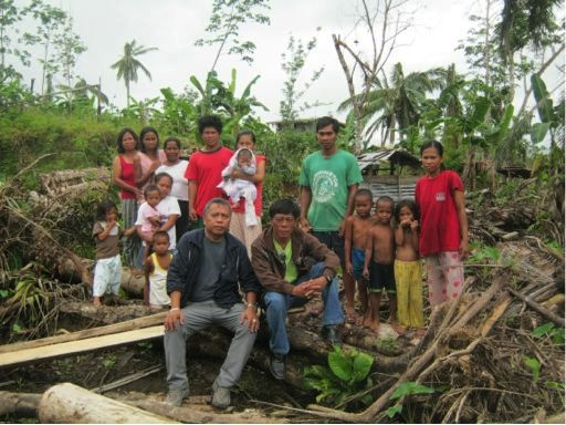 Survivors of the Typhoon grimly stood together amongst the destruction of their homes.