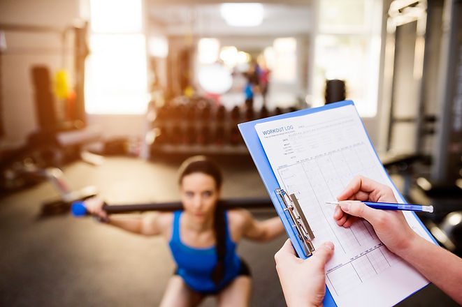 Woman exercising in gym, personal traine