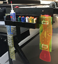 The Long Arm Rack is held by magnets to the side of a longarm sewing machine.