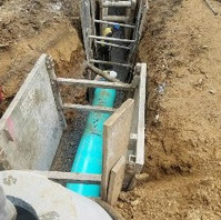 Contractor Installing 21-inch sanitary pipe into a manhole.