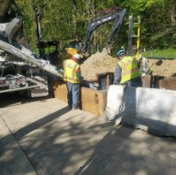 Contractor excavated around 27-inch PCC pipe and formed to cast concrete manhole MH8-2 base.