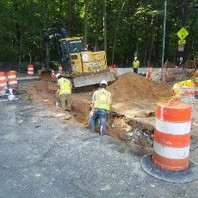 Contractor backfilling operation after concrete conduit encasement by corner of Rittenhouse and Oregon Avenue.