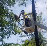 Utility Contractors transferring utility lines to the newly installed PEPCO poles.