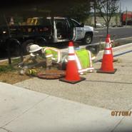Pulling wire through MH on sidewalk at MLK & Raleigh St, SE Northbound.