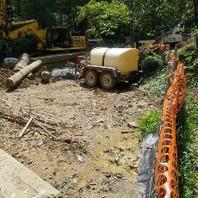 Contractor placing filtration bag to mitigating Creek sediment runoff pollution.