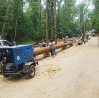 Contractor preparing 24-inch steel casing pipe to be placed across the creek under bed.