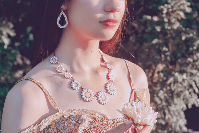 woman wearing daisy necklace and rhinestone teardrop earrings