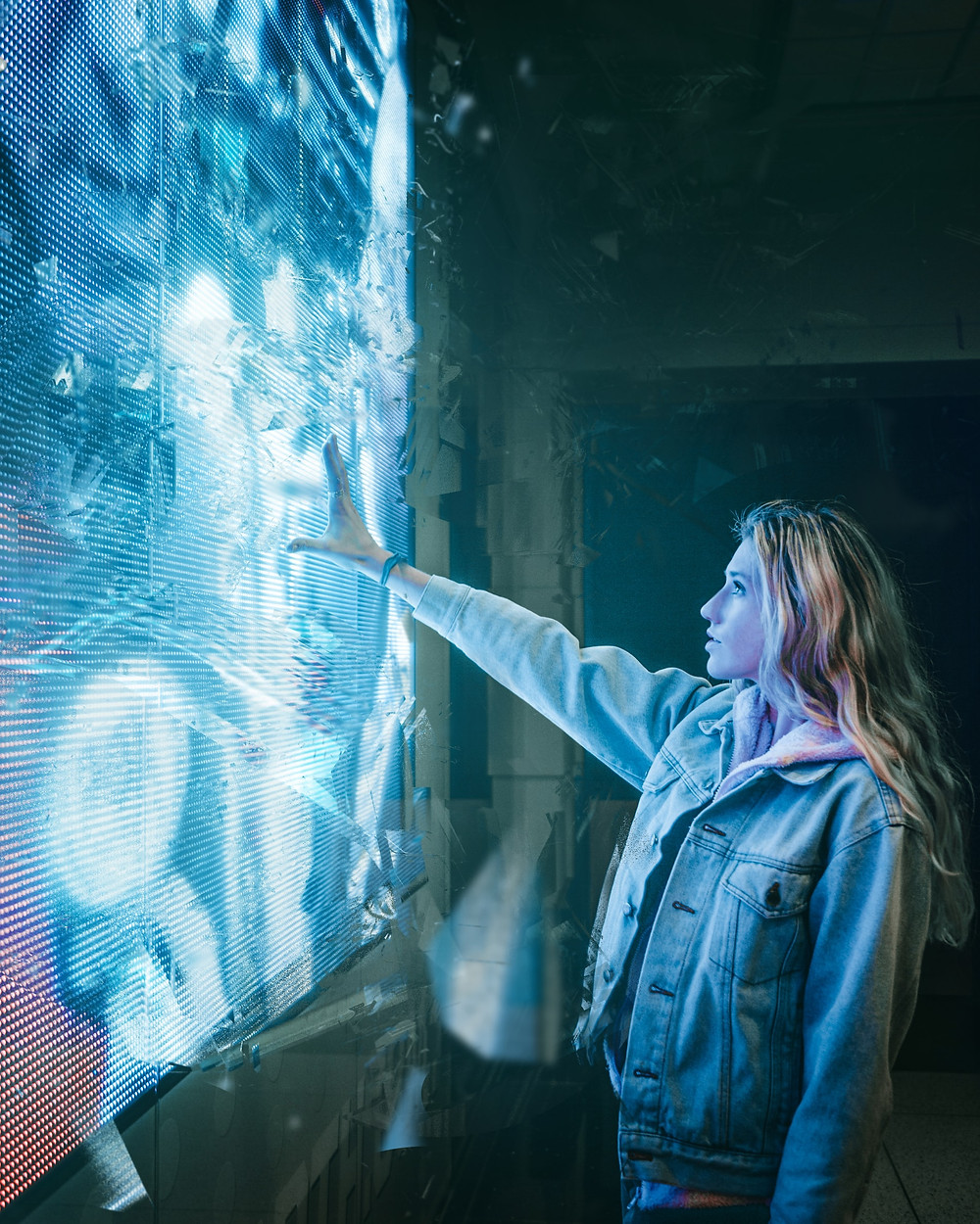 Woman in urban clothing touching a large, blue artificial screen.