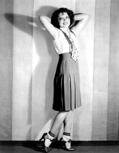 Clara Bow with her arms behind her head, smiling