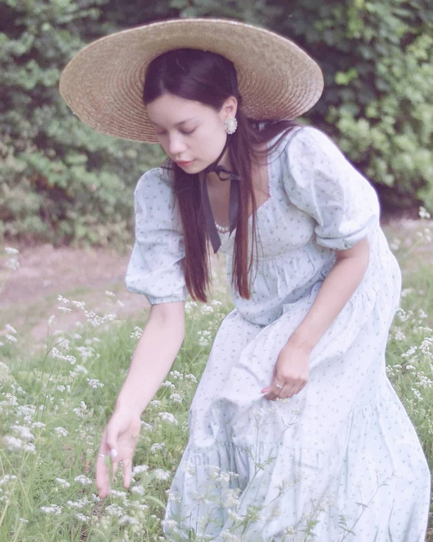 Romantic woman picking cow parsley from a field.