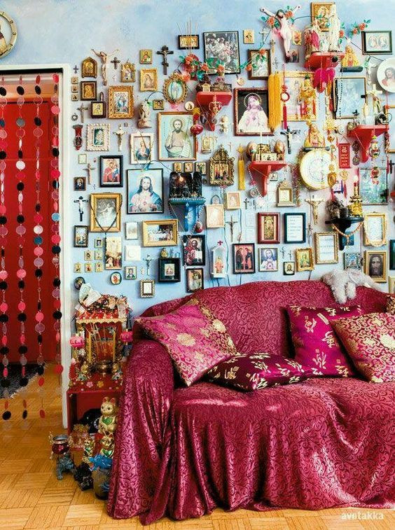 Photo of well decorated interior. Picture frames on every part of wall, red sofa with fabric thrown over.