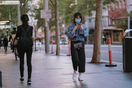 Asian woman on pavement wearing mask using mobile phone.