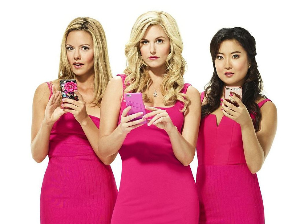 Three girls in pink holding phones and staring up at you. They look judgemental.