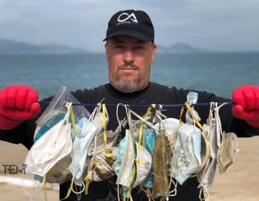 Man holding face masks found on beaches.