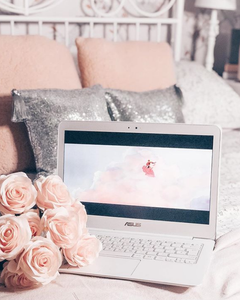 Open laptop with pink flowers and an animation on screen.