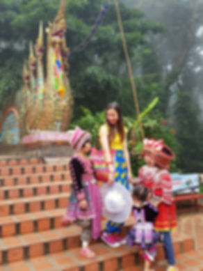 Image of a fashion blogger and some Thai tribe children stading on the steps of Doi Suthep, Chiang Mai, Thailand.