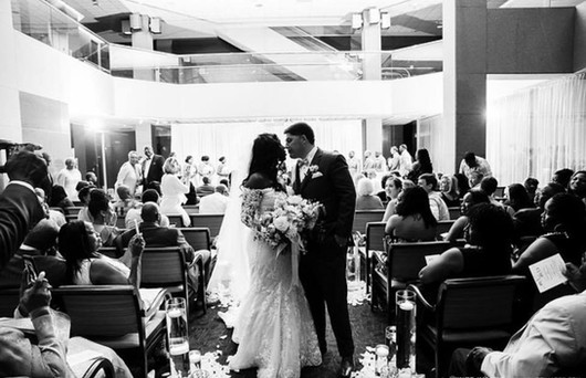 Guests look on as the bride and groom share a kiss at the Harbert Center