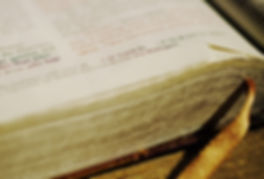 An artistic photo showing part of a page of an open Holy Bible with a place holder ribbon protruding out from pages below.