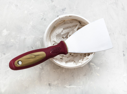 metal-spatula-on-container-with-putty-PY