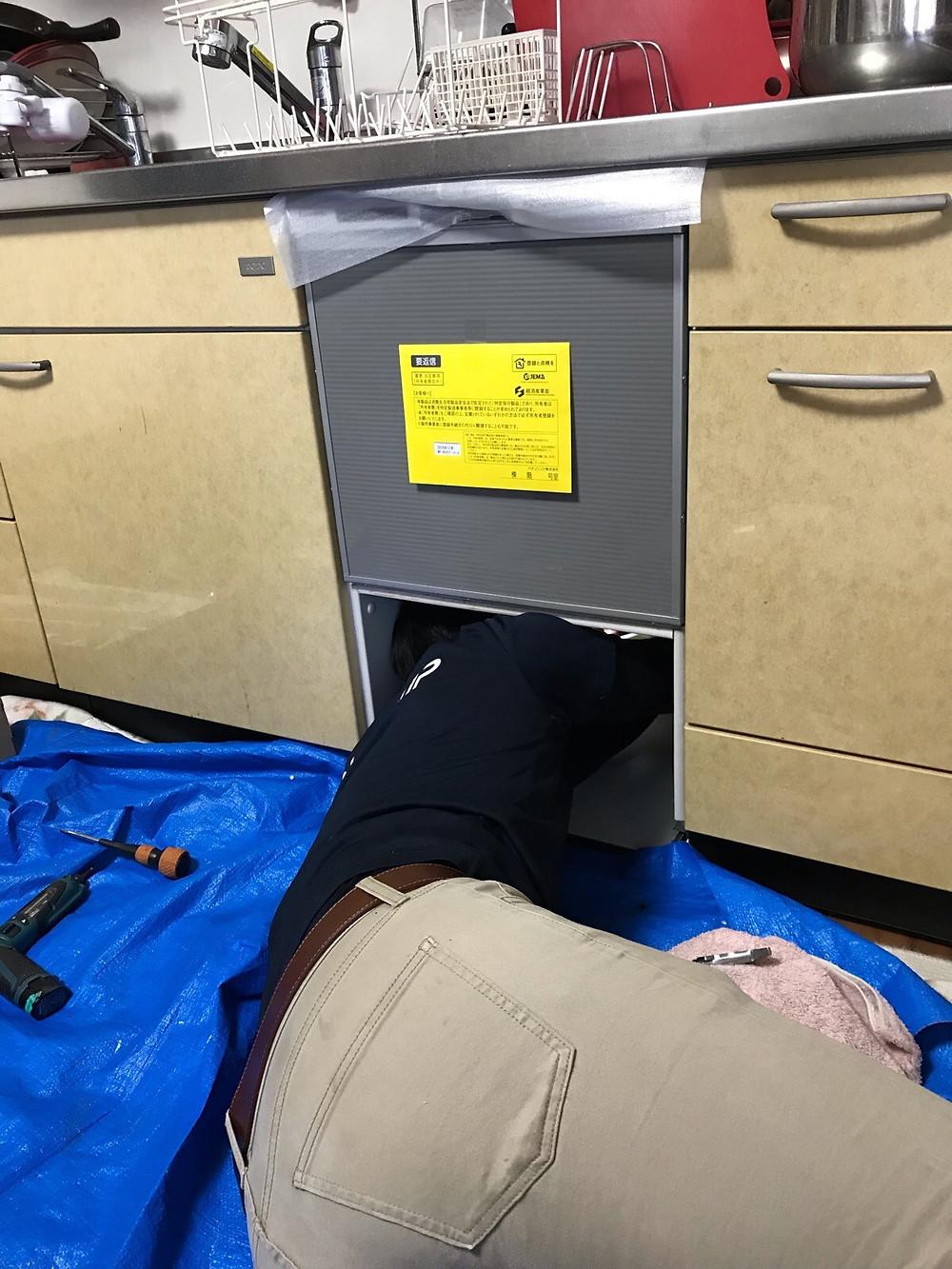 下準備の後、新しい衣食器洗い機をはめ込み、配管の接続を行っているところです。