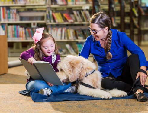 Down syndrome child with teacher, dog and book having fun.
