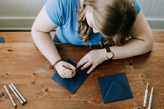 Woman doing calligraphy on a navy envelope