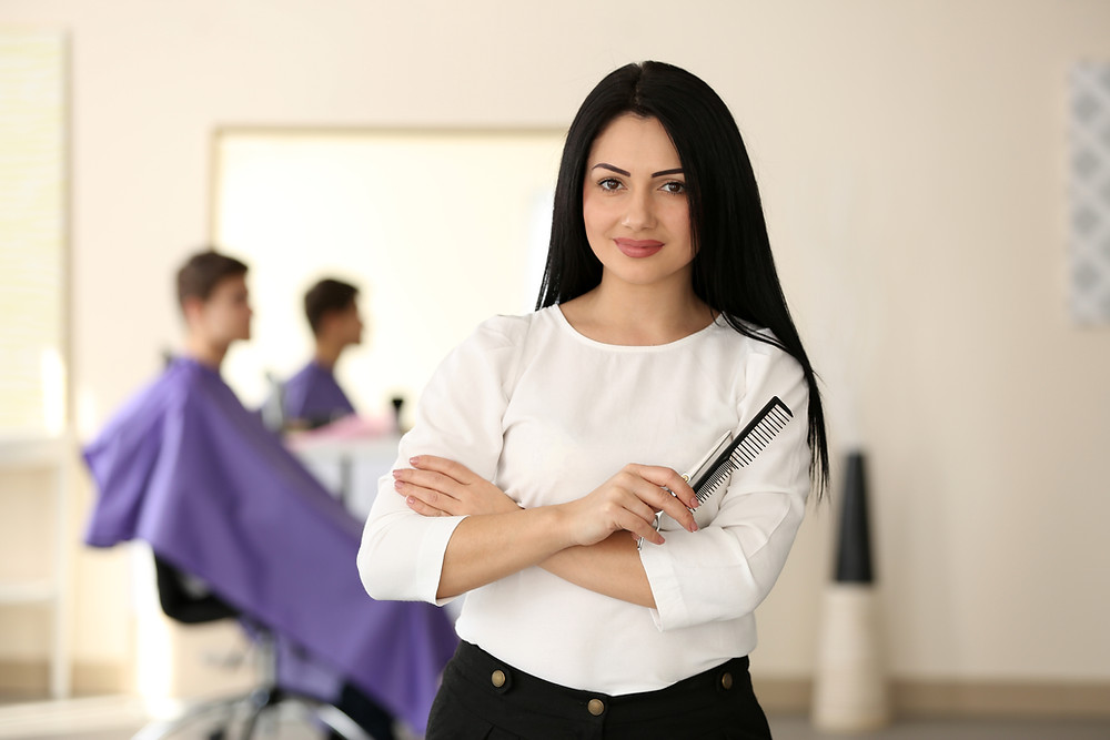 Black haired hairdresser holding a pair of scissors and a comb
