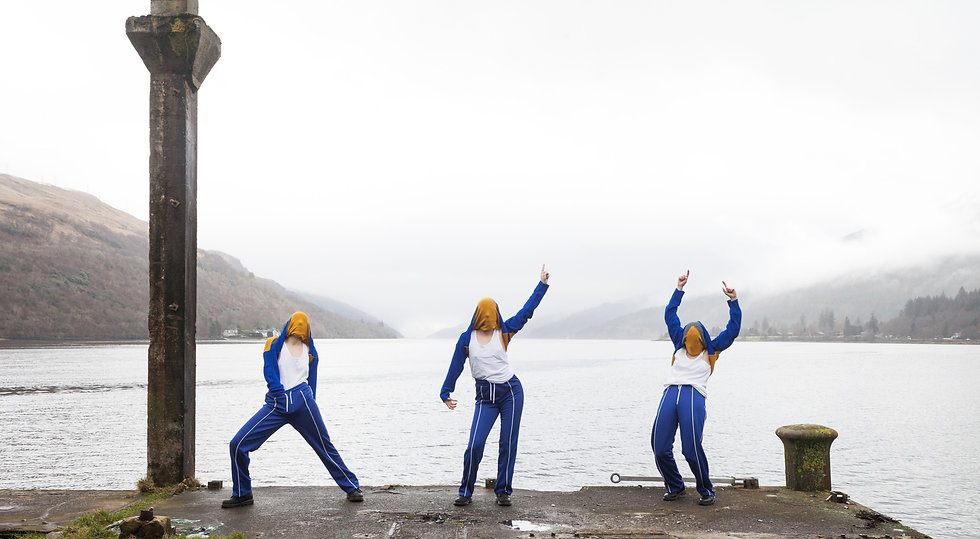 3 mysterious dancers in blue and white sports gear pose in front of a misty loch. They have pulled their jumpers over their heads so you cannot see their faces.