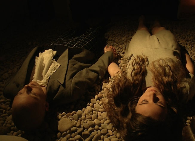 Two people lie down on a bed of stones, they are holding hands.