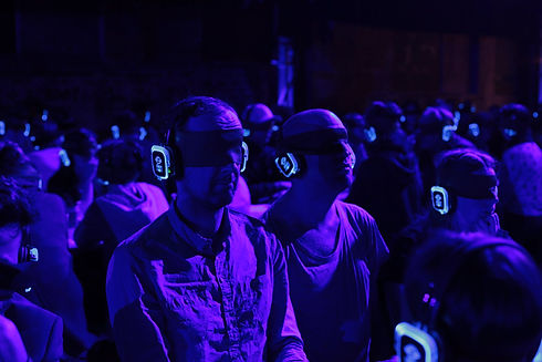 Two audience members sit in a dimly lit warehouse, they are blindfolded and wearing headphones that glow in the darkness.