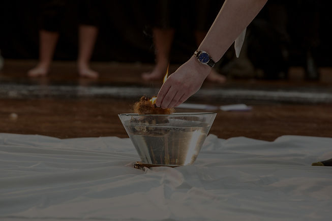 A white sheet covers the floor, ontop a clear glass bowl is full of water. A hand reaches down and puts a flaming ball of hair into the water.
