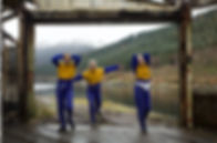 Three women in blue and yellow sports wear stare at the camera as they walk towards it. Behind them a misty loch and forest contrast the striking blue and mustard figures.