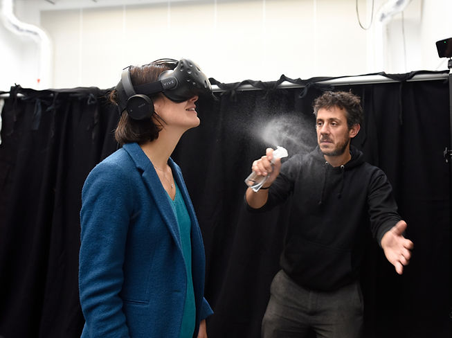 A woman wears a VR headset, she smiles as a man moves infront of her to mist water towards her.