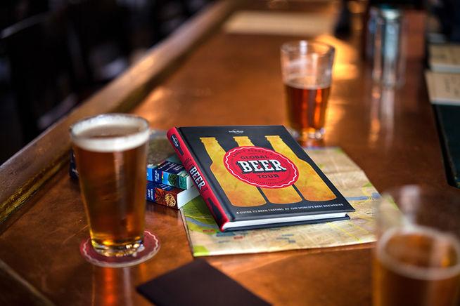 Bière sur comptoir avec livre de voyage