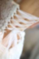 Robe de mariée dos nu lacé Quiqui Lamothe  en dentelle fine à bouquets, la dentelle découpée retombe sur la jupe taille basse, esprit bohème