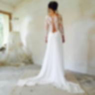 Robe de mariée dos nu Quiqui Lamothe, esprit décontracté chic avec un haut de dentelle fine à manches ouvert vers le bas du dos et une longue jupe fluide taille basse drapé de dentelle sur les hanches