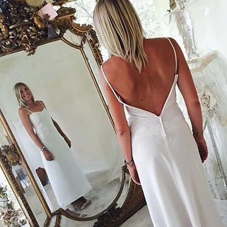 Robe de mariée simple dos nu Quiqui Lamothe à bretelles fines, épurée, en soie fluide, juste soulignée par ungalon de dentelle sur les hanches et quelques petits boutons pour fermer la robe