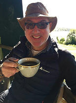 Photograph of Tigger, a cis man in his mid 50s, wearing a hat, sunglasses and drinking a coffee