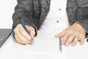 ノートにペンをもって書いている人