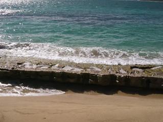 Ecume offrande ! Le bleu de l'eau se casse en bris de verre blanc sur les rochers noyés, jamais sauv