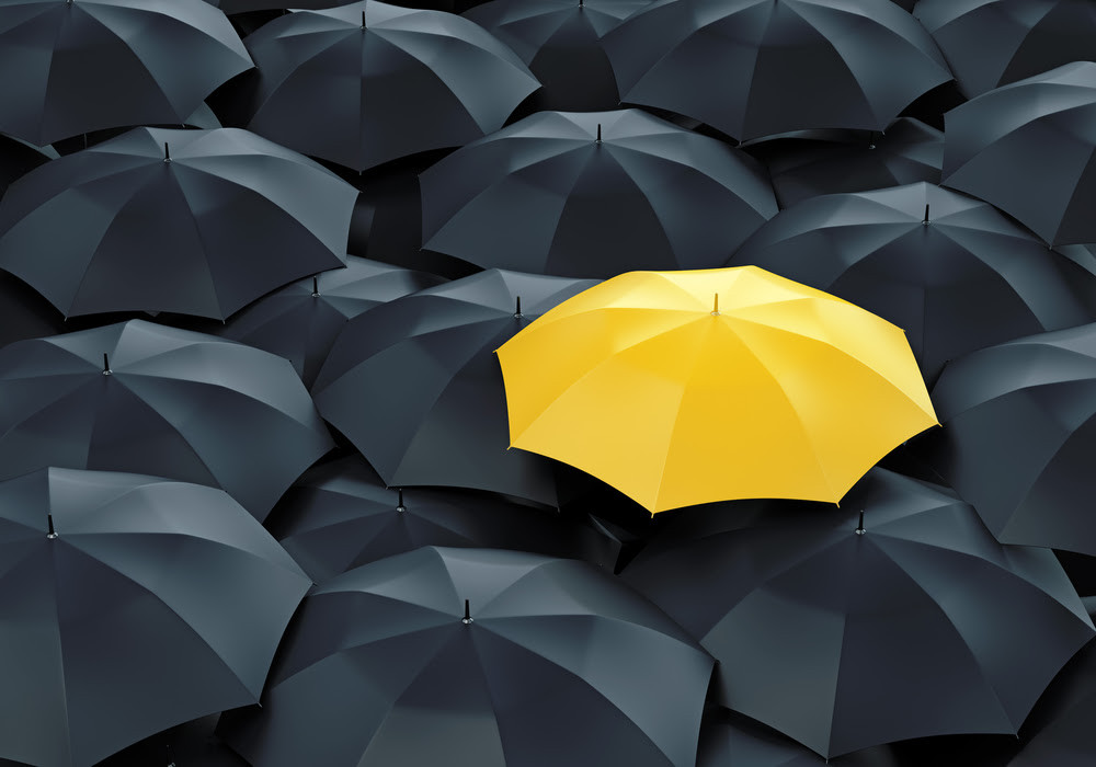 Yellow umbrella in a sea of black umbrellas.