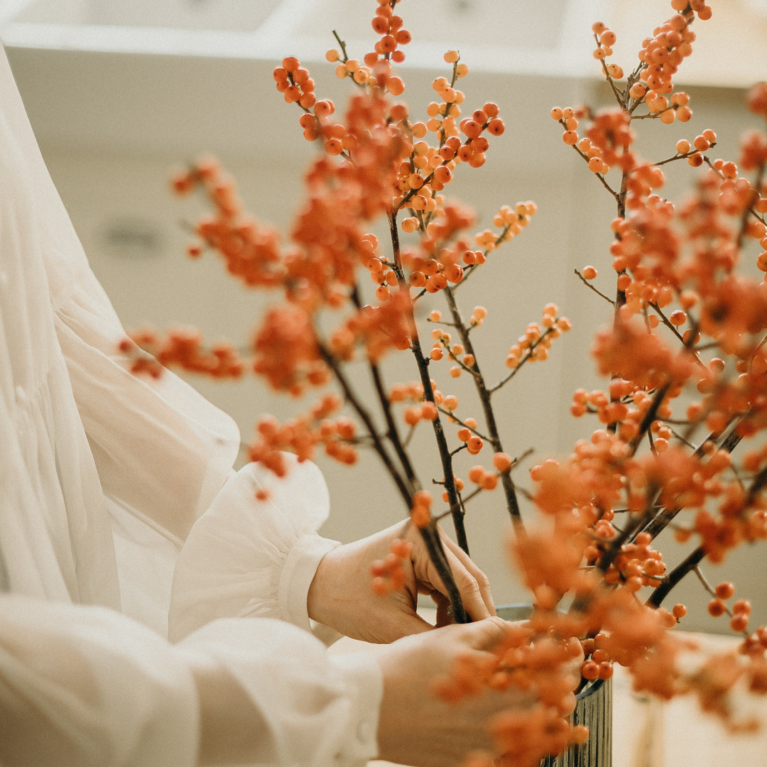 woman-arranging-flowers-on-a-vase-315430