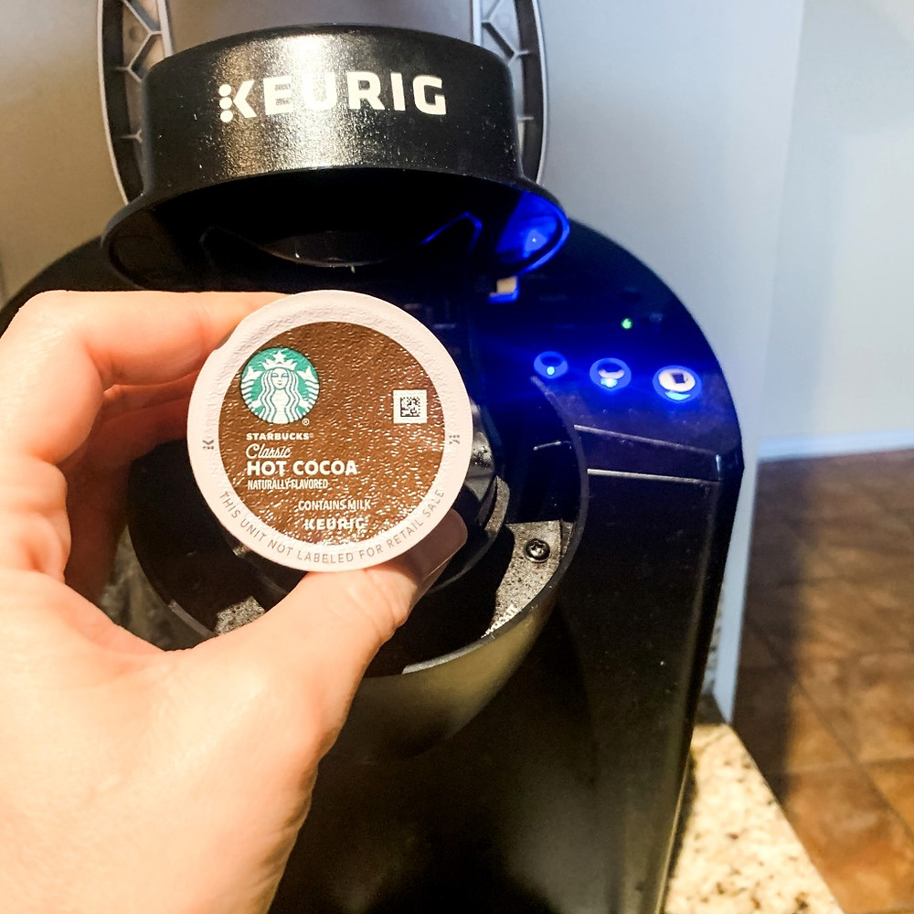 Keurig machine with a person's hand holding a Starbucks hot cocoa cup