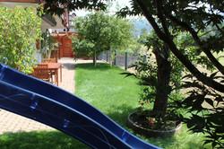 Erdterrasse mit Spielplatz, Gartenlaube und Obstbäumen.