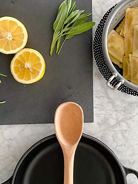 bancada com massa, limão siciliano, sálvia e uma panela