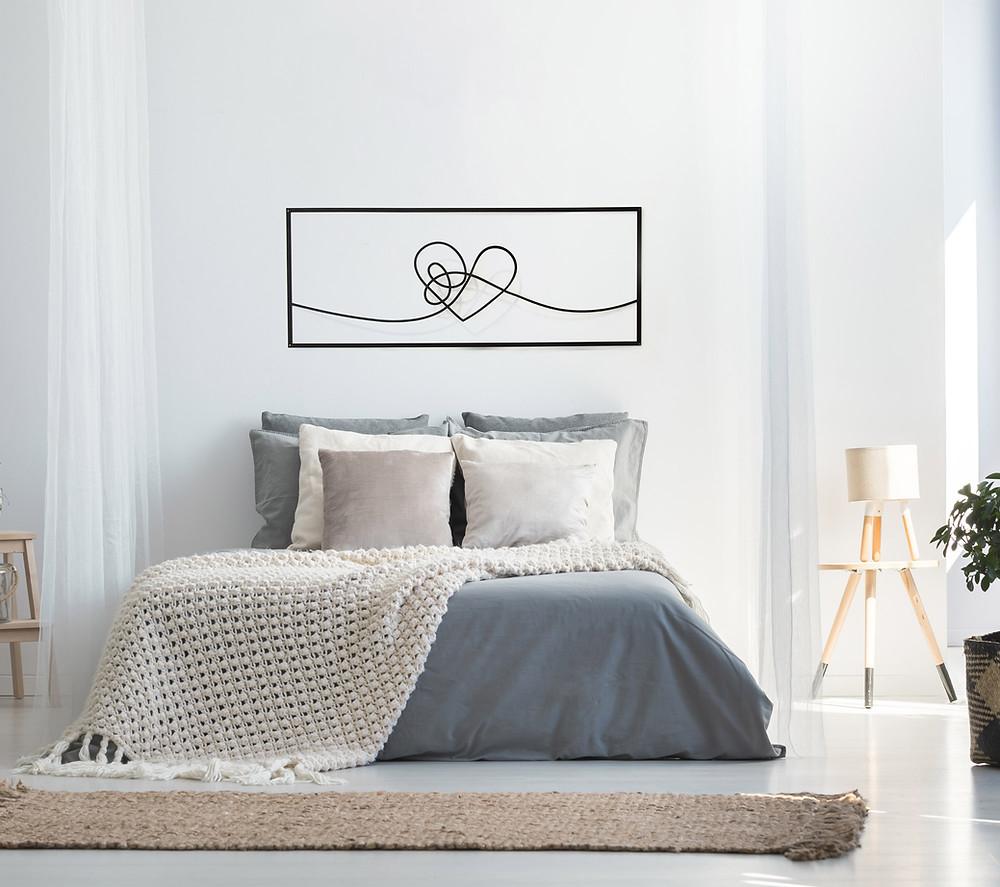 תמונת לב ממתכת מעל מיטה