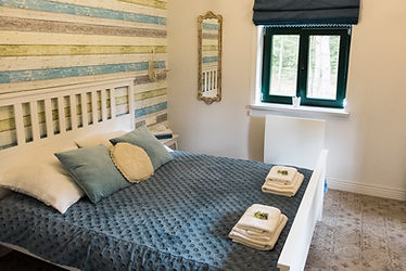 wygodna i elegancka sypialnia z dużym podwójnym łóżkiem na parterze