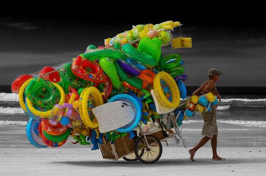 Homem arastando carroça de bolas infláveis na praia. Man raking cart of inflatable balls on the beach.